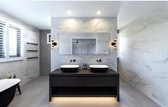 Black vanity with twin white basins, matte black tap and mixer, black stand alone bathtub, white and grey marble walls. Matte black towel rack. Project by - @bighouselittlehouse #taps #interiordesign #bathroom #australia #architecture #bathroomdesign #bathroomcollective Visit our website for more www.bathroomcollective.com.au