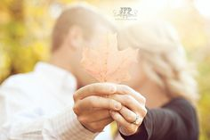 love the idea of us kissing and holding up a leaf blocking our face...maybe even have our wedding date written on the leaf? Fall engagement session