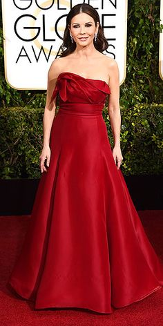 11 Must-See Red Dresses From the Red Carpet | CATHERINE ZETA-JONES | Bombshell waves? Check. Megawatt H. Stern diamonds? Check. Siren-esque strapless gown in a rich wine hue? Check. Catherine Zeta-Jones checks all her signature boxes in this look.
