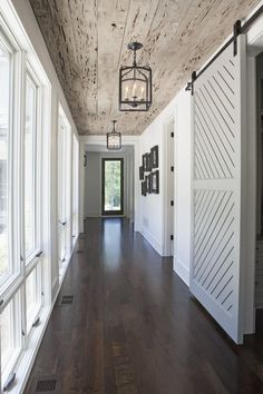 Check out this rustic hallway! Dark wood floors with the reclaimed wood ceiling. The white sliding barn door adds a dramatic effect. The cage pendant lights down this hallway gives it a dramatic and gorgeous look! Add some rustic elegance to your home! Deco Design, Design Case, Book Design, Design Design, Style At Home, Barn Door Designs, House Ideas, Dark Wood Floors, Dark Hardwood