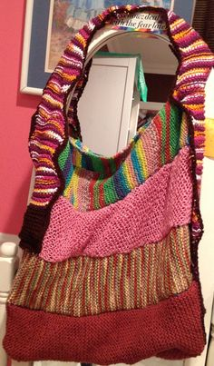 A tote bag made out of knitted scarves