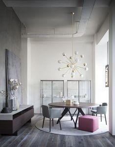 Sala de jantar cinza, com móveis leves, lustre ousado e um pufe rosa