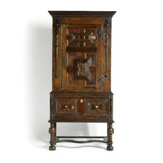 AN OAK AND EBONISED ONE-DOOR CUPBOARD ON STAND CHARLES II, 17TH CENTURY AND LATER  with protruding stepped cornice and raised panelled central door, the stand with one drawer set with two raised panels, on curved stretchers and ball feet, alterations height 198cm., width 97cm., depth 44cm.