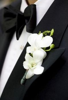 The groom's boutonniere will be white dendrobium orchids wrapped in pewter ribbon.