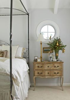 A vase bursting with evergreen sprigs and small golden pears adds just the right amount of holiday cheer to this bedroom. - Traditional Home®