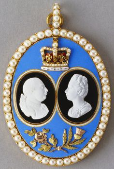 Large oval pendant with two small white cameo profiles of George III and Queen Charlotte applied to black enamel ovals, mounted on pale blue enamel plaque with applied crown above and entwined rose and thistle below; all within a border of seed pearls. Cypher in gold on reverse.