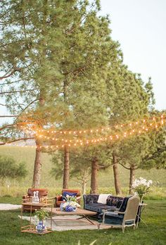 An outdoor lounge area with mismatched furniture and glowing café lights | Brides.com