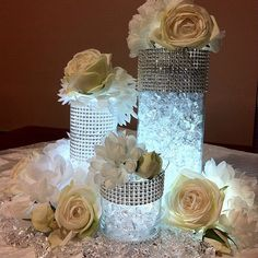 This one looks a little cheap, but possible to do nicely???    So easy to do and it looks very elegant. A few glass cylinders wrapped in crystal bridal trim, some battering operated lights under the bottom of your glass rocks and simple touch of flowers.    Image by weddingsbycolor