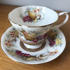 """Royal Albert Vintage Teacup and Saucer Pattern """"Devon"""" Country Fayre Series This is a unique Royal Albert teacup and saucer in the Chelsea shape. This set is a milky brown with a garland of yellow flowers, pears, red cranberries and mushrooms. This set is trimmed in gold on the edges,"""