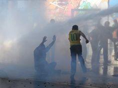 18/03 - Manifestantes que permaneciam ocupando a Avenida Paulista, em São Paulo, correm após a tropa de choque jogar jatos d'água para desocupar a via (Foto: Felipe Rau/Estadão Conteúdo)