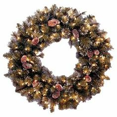 """Pre-lit faux pine wreath with pinecone and snowflake accents. Features clear lighting.   Product: WreathConstruction Material: PVC and metalColor: MultiFeatures:  Pre-lit with 50 clear lightsTrimmed with pine cones and snowflakesSuitable for indoor or outdoor use Dimensions: 24"""" DiameterNote: Spare bulbs and fuses are included"""