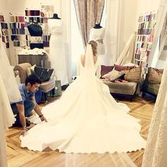 Una última prueba, en el probador de Manuel de Vivar enseñando a la novia a sentarse y a las acompañantes a colocar la cola del vestido www.bodasytendencias.com