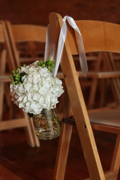 Great wedding idea! Flowers hung with ribbons in jars or tin buckets to decorate pews!