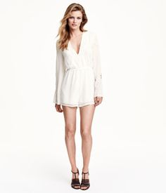 V-neck playsuit in light chiffon crêpe with openwork embroidery, a tie and concealed zip at the neck, elasticated seam at the waist, long, gently flared sleeves and short legs. Unlined.
