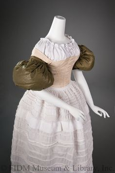 "1830s undergarments: To keep the enormous sleeves of the dress from collapsing, large cotton pillows, called ""plumpers"" filled with eiderdown attached at the upper arms. Corded petticoats were worn to support the full skirt. Like the corset cording, the insertion of cotton ropes into casings around the petticoat made the material firm, yet flexible. Only after these undergarments were secured was the outer gown slipped over a woman's head and settled onto this ideal foundation."