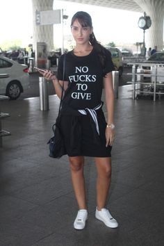 """Nora Fatehi's airport style is quite chic but her T-shirt does all the talking. The quote on her tee read """"No F***** To Give"""" which is cool."""