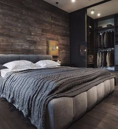 Contemporary brown bedroom with an opulent Italian-style bed and wood details on the wall. Together with a closet right by the bed's side, this is a perfect example of how a contemporary can be cozy too.