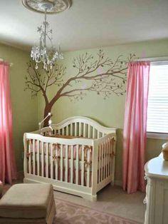murs en vert pâle et rideaux roses dans la chambre de bébé fille