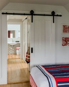 Barn door to small walk-through closet (wardrobe on either side as hallway splits it) into master bathroom, which has its own hidden sliding door, giving the illusion of only one door (the catty corner one)
