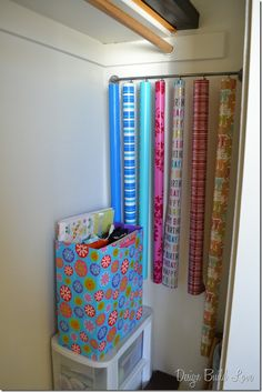Gift wrap storage -- curtain clips for wrapping paper tubes, and a wrapped box for bags and bows.  Would add bungee cord to stop rolls from swinging.
