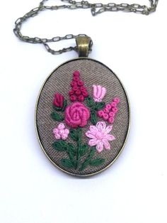 Hand embroidered pink flower bouquet on a cream fabric with color cotton embroidery thread and put into vintage bronze style cameo base. This bohemian necklace will be a lovely addition to any outfit. It will make you feel special whatever you were. Fabric Necklace, Floral Necklace, Bohemian Necklace, Bohemian Jewelry, Embroidery Jewelry, Hand Embroidery Patterns, Ribbon Embroidery, Pink Flower Bouquet, Pink Flowers