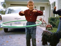 """Hoop-De-Do: 1958 words from the little fellow hoopin' today: """"This is me in the summer of 1958 in Bedford Quebec, during that year's Hula Hoop craze. As you can see, Mom sure did dress me in a weird way -- buttoned-up collar, full cuffs and elastic band pants? Our cocker spaniel Cindy is in the background"""""""