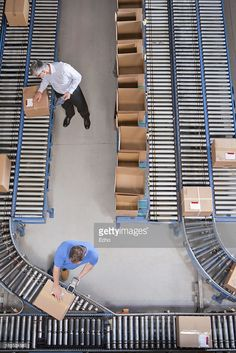 Stock Photo : Workers packing boxes on conveyor belts in distribution warehouse