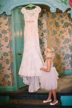 Flower girl looking at Bride's dress. To frame and give as a gift to the flower girl on her wedding day!
