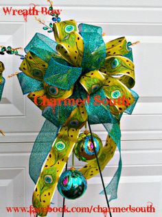 Wreath bow in a peacock theme - accented with ornaments and floral shooters.  BLING BLING!  Follow us at www.charmedsouth.etsy.com www.facebook.com/charmedsouth christma wreath, christma bow, ornament, christma idea, theme christma, wreath bow