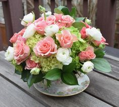 Floral tea cup with spray roses, ranunculus and hydrangeas. A neat flower arrangement/floral piece.