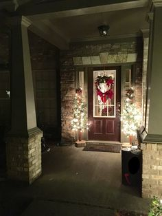 Mini Lighted Christmas trees flanking front door with natural twig and cranberries wreath
