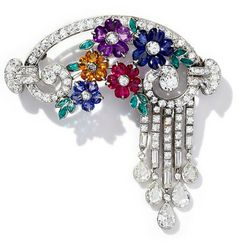 Multi Gem Flower Brooch with ruby, sapphire, citrine & amethyst flowers, each flower centred by a diamond, the petals formed from the gemstones, within an arched diamond frame. The 5 articulated drops suspending pear shaped diamonds can be removed, English, circa 1935.