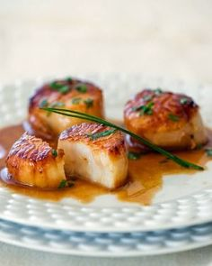 Carmelized Scallops 12 large scallops    Pinch kosher salt    Freshly cracked pepper    4 tablespoons clarified butter*    1/2 cup white sugar spread on a flat plate    ½ cup dry white wine    1 fresh lemon, squeezed    1 tablespoon finely chopped flat Italian parsley    8 chives    1 tablespoon lemon zest