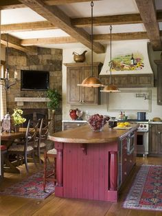 Love the cabinets, wood beams and stone fireplace. I also like the idea of a color on the island.