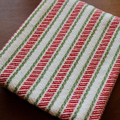 Overview: A handwoven kitchen towel, with Christmas candy cane stripes running the length of the towel. Wrap this towel around a bottle of wine for a hostess gift that will last! (see photo 10) Size: A generous 31 inches by 19 inches. Style: Woven, by hand, in undulating twill.