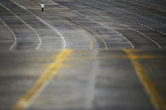 A policeman walks on an empty 20 lane road leading to the country's parliament building in Naypyitaw, Myanmar, November 11, 2014. REUTERS/Damir Sagolj
