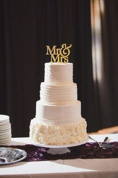 Four-tier wedding cake with different frosting designs + gold cake topper {Meysenburg Photography}