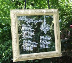 butter yellow vintage framed mirror seating chart for intimate wedding. chandelier detail