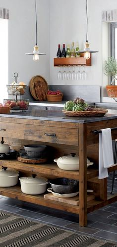 Reclaimed Wood Kitchen Island: Like a treasured vintage find or a custom-designed piece, this elegant kitchen island serves as a rustic yet refined workstation for the home cook or entertaining enthusiast. Bluestone is crafted with reclaimed pine from old buildings and doors and a lustrous slab of bluestone. #reclaimedwood #rustickitchenisland #rustickitchen #farmhousekitchen