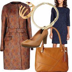 Una donna fashion che indossa abito a sacchetto blu, gioielli quali il girocollo prezioso e l'anello, soprabito marrone a fantasia con cintura in vita e scarpe e borsa color cuoio.
