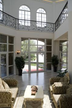 Wrapped in exterior glass, this marble floor living room is overlooked by a ring of upper level walkway. White surroundings are spiked with black wrought iron railings, with array of ornate, traditional furniture at center. TB I LOVE THIS BANNISTER