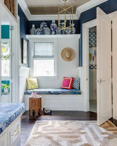 Well appointed white and blue mudroom is lit by a brass pendant hung from a ceiling clad in taupe grasscloth wallpaper over an ivory and beige trellis rug.