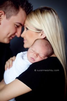 Portrait for father, mother and newborn. Newborn on shoulder, parents touches noses smiling.