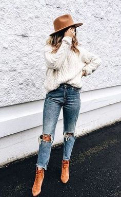 Oversized white knit sweater with blue jeans, tan boots and hat.