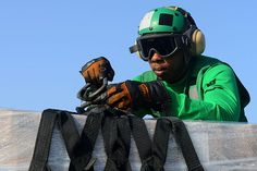 A Sailor removes a cargo net from a pallet of stores aboard the aircraft carrier USS John C. Stennis (CVN 74) during a replenishment-at-sea. John C. Stennis is deployed to the U.S. 5th Fleet area of responsibility conducting maritime security operations, theater security cooperation efforts and support missions for Operation Enduring Freedom. (U.S. Navy photo by Mass Communication Specialist 2nd Class Kenneth Abbate/Released)