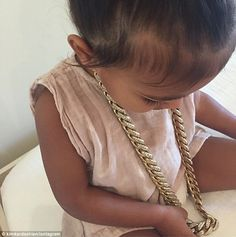 Already into jewelry: Kim Kardashian shared this image on Friday of daughter North wearing father Kanye West's yellow gold and diamond necklace. The 34-year-old captioned the image,'No daddy it's me necklace'