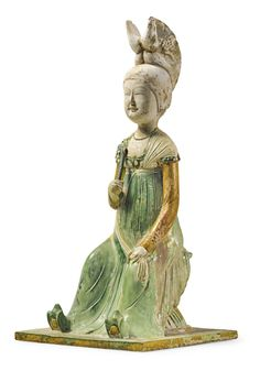 RARE, IMPORTANT SANCAI-GLAZED POTTERY FIGURE OF A COURT LADY, TANG, exquisitely modeled, elegant, sitting on a rattan stool, wearing a green-glazed skirt, green slippers with amber-glazed soles, and a simple beaded necklace, the left hand resting on one knee and holding a cream-glazed shawl, the right hand holding a flower, the face with delicate features and the hair bound in an elaborate winged coiffure with a floral ornament, all supported on a square green and ochre-glazed plinth, H 16""