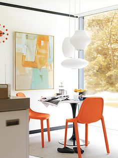 Mid Century Modern inspired dining… I like the pop of orange from the chairs. Plus that abstract art is gorgeous!