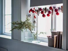 Un store décoré pour Noël, Suspendues à différentes hauteurs par un fil rapidement cousu sur le bord du store, des boules rouges et argent, et quelques pommes de pin lamées plantent le décor. Simple et efficace.