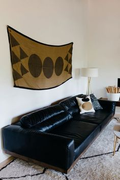 A Temple print from Block Shop Textiles hangs above the black leather sofa from Four Hands.